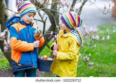 Two little kids boys and friends making traditional Easter egg hunt