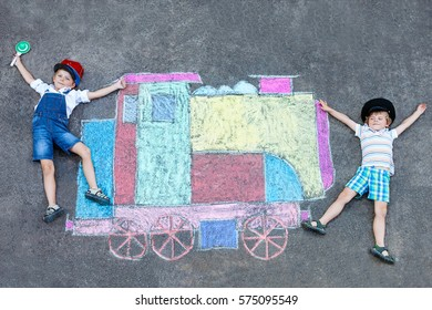 Two little kids boys having fun with train or steam locomotive picture drawing with colorful chalks on ground. Children, lifestyle, fun concept. funny friends playing and dreaming of future profession