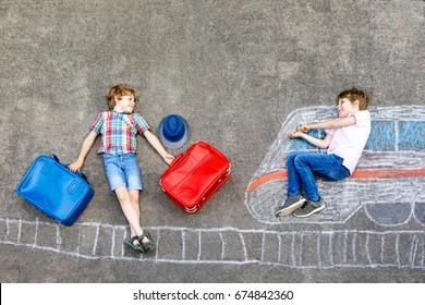 Deux petits garçons s'amusant avec des images de train dessinant avec des craies colorées au sol. Enfants s'amusant avec la peinture à la craie et au crayon et jouant en vacances. Amis avec valises.