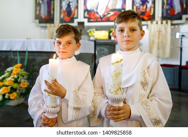 Two little kids boys receiving his first holy communion. Happy children holding Christening candle. Tradition in catholic curch. Kids in a church near altar. Siblings, brothers in white gowns.