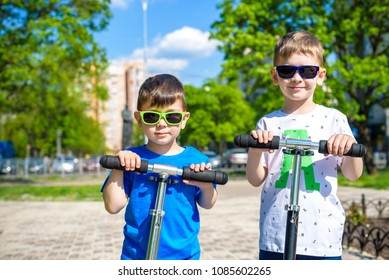 Two little kids boys riding on push scooters. Warn summer or spring day. Brothers kid boy having fun together wearing sunglasses. Friendship concept.