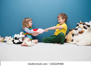 Two little kids, brother and sister fighting over a toy. the conflict between children.