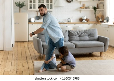 Two little kids brother and sister hold young father not letting go show affection bonding, small children siblings attached to dad, undergo parents divorce, suffer from psychological family drama