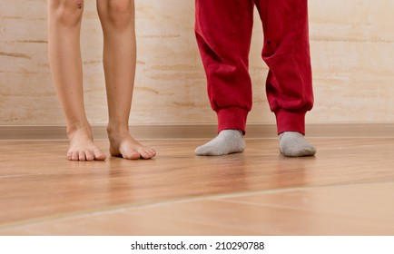 Two Little Kids Feet Isolated on Wooden Background.