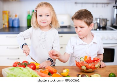 Two little kids helping at kitchen with salad making