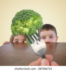 Two little kids are hiding behind a table from a fork with a healthy piece of broccoli on it for a childhood nutrition or picky eater concept.