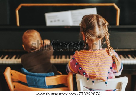 Two little kids playing on piano, toddler girl and baby boy practicing music at home, back view
