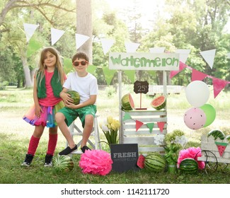 Two little kids are selling watermelon fruit at a homemade stand on a sunny day with a price sign for an entrepreneur concept
