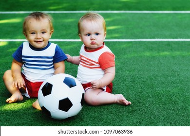 Two little kids sitting at football field with a soccer ball. Children (boy and girl) playing with a ball at sports ground. Summer outdoor activity concept. Room for copy text