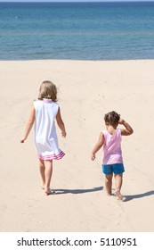 Two little kids walking in the sand on a beach
