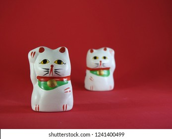 Two little Maneki Neko, Japanese lucky cats, amulets that bring good luck, protection, prosperity, health and happiness. The cat in the foreground is well focused. The other, behind, is out of focus.