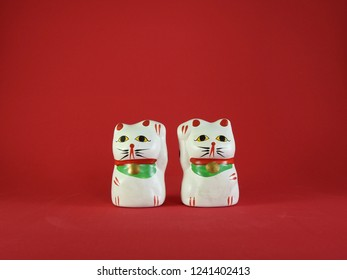 Two little Maneki Neko, Japanese lucky cats, amulets that bring good luck, protection, prosperity, health and happiness. Red background.