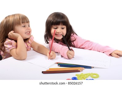 Two little preschool girls drawing with colorful pencil crayons