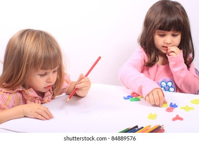 Two little preschool girls, one drawing with pencil the other playing with letters