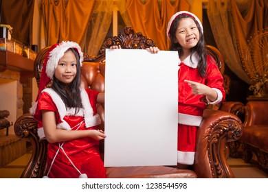 Two little santa girls with blank white board
