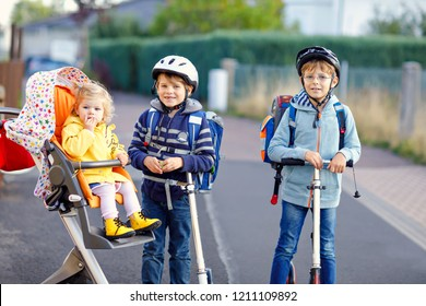Two little school kid boys and cute toddler girl going to school. Tiny child sister sitting in pram. Brothers riding on scooter. Happy healthy amily of three children.