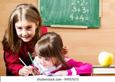 Two little schoolgirls in classroom