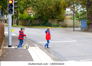 Two little schoolkids boys running and driving on scooter on autumn day. Happy children in colorful clothes and city traffic crossing pedestrian crosswalk with traffic lights.