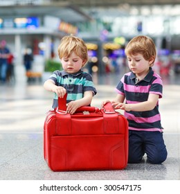Two little sibling boys having fun and going on vacations trip with suitcase at airport, indoors.