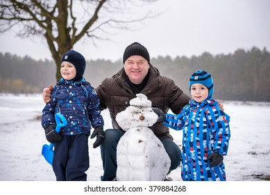 Two little siblings boys making a snowman with grandfather, playing and having fun with snow, outdoors on cold day. Active outdoors leisure with children in winter.