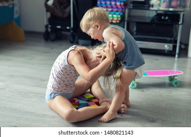 Two little siblings children quarrelling after playing at room at house. Crying offended toddler boy arguing with elder sister. Family rivalry and generation conflict concept