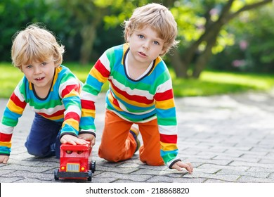 Two little siblings, kid boys in colorful clothing with stripes playing with red school bus toy in summer garden on warm sunny day. Learning to play and communicate together.