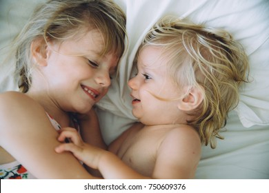 Two little sisters in bed laughing