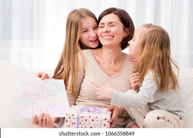 Two little sisters congratulate their mom with Happy mother's day. Children hugging and kissing mother and giving her creative hand-made drawing and gift box