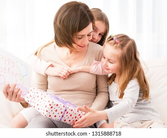 Two little sisters congratulate their mom with Happy mother's day. Children hugging and giving her creative hand-made drawing and gift box