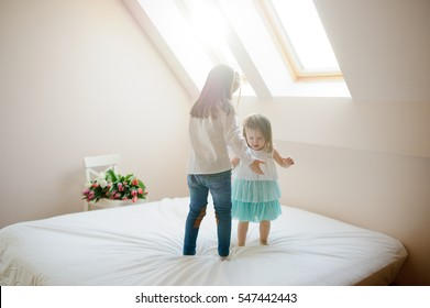 Two little sisters dance on a big bed. To girls it is very cheerful. On a white chair the big beautiful bouquet of tulips lies. From a window the sunlight flows.