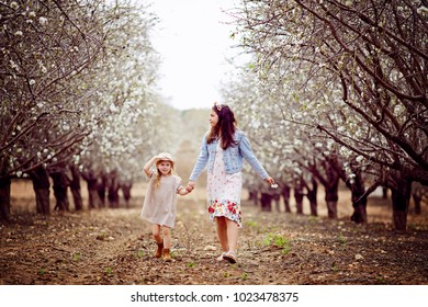 Two little sisters dressed in white holding each other hands and dancing outdoors in the park