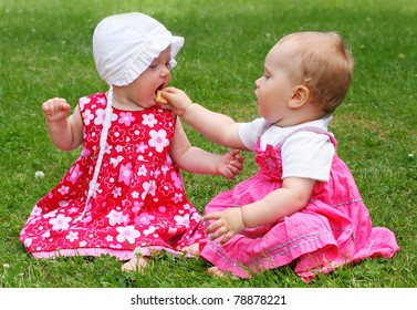Two little sisters eating on a grass.