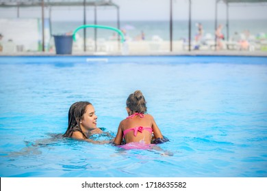 Two little sisters girls are swimming in a large pool with clear blue water of mine near the hotel on the background of the sea and the beach. Concept vacation tropical hot country with children