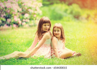 Two little sisters have a fun and hugging in summer garden, Poland, Wroclaw