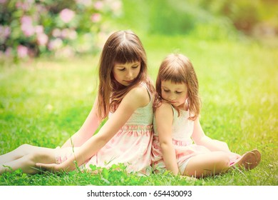 Two little sisters have a fun in summer garden, Poland, Wroclaw
