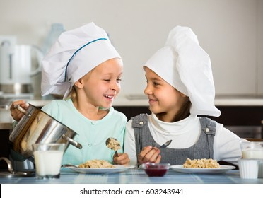 Two little sisters having breakfast with oatmeal porridge indoors