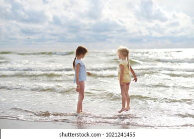 Two little sisters having fun on a sandy beach on warm and sunny summer day. Kids playing by the ocean. Summer activities for children.