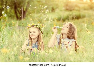 Two little sisters having fun playing with soap bubbles during sunny summer day