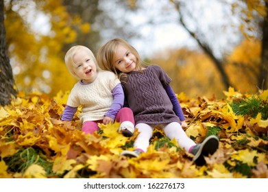 Two little sisters having fun in beautiful autumn park