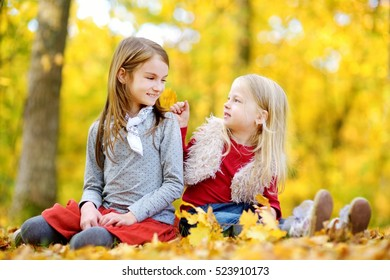 Two little sisters having fun together in beautiful autumn park on a sunny day