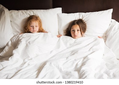 two little sisters lie in the bed under the linen