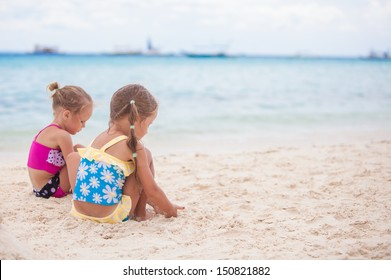 Two little sisters in nice swimsuits playing on sandy beach