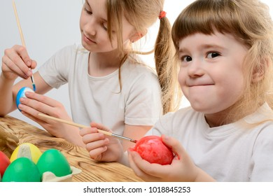 Two little sisters painting colorful Easter eggs