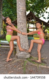 Two little sisters playing on the beach around a coconut tree!