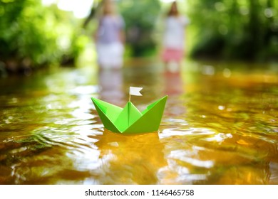 Two little sisters playing with paper boats by a river on warm and sunny summer day. Children having fun by the water. Summer activities for small kids.