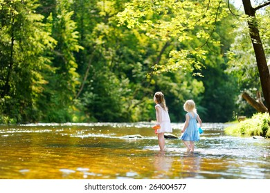 Two little sisters playing with paper boats by a river on warm and sunny summer day