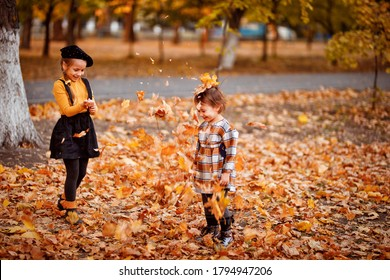 two little sisters playing with yellow fallen leaves in autumn Park. walking and playing in nature.