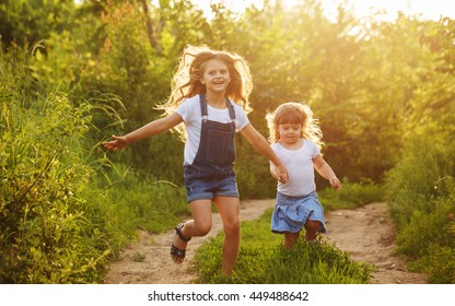 Two little sisters run on the road in park on a sunny summer day. Family time. Cute babies. Soft focus