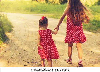 Two little sisters run on the road in park on a sunny summer day.  Cute little girls. Soft focus