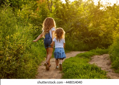 Two little sisters running on the road in the park on a sunny summer day. Family time. Cute babies.